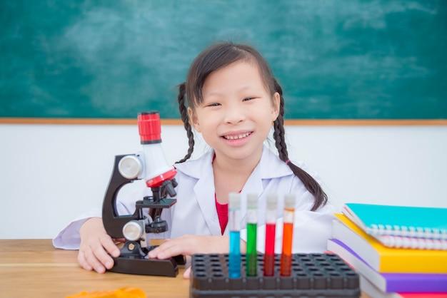 Маленькая девочка в пальто и держит микроскоп