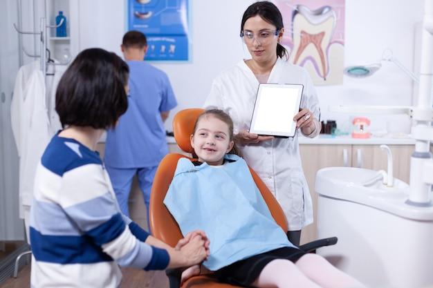 흰색 화면이 있는 장치를 들고 있는 부모와 의사와 치과를 방문하는 과정에서 턱받이를 입은 어린 소녀. 태블릿 pc w를 들고 엄마와 아이에게 치아 예방을 설명하는 stomatolog