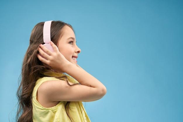 Little girl wearing earphones, listening music and smiling