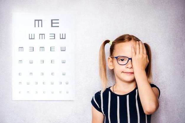 한 손으로 눈을 가리고 있는 안경을 쓴 어린 소녀가 학교 전에 시력 검사를 하고 배경에 흐릿한 눈 차트를 가지고 있습니다