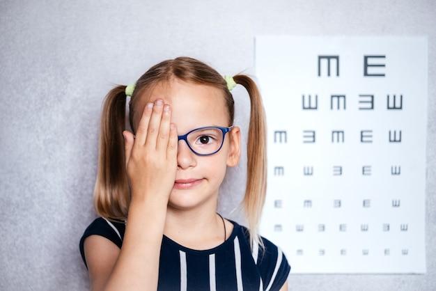 Маленькая девочка в очках принимает тест на зрение перед школой с размытой диаграммой зрения на заднем плане