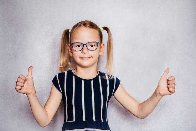 親指を立てて眼鏡をかけている少女、子供の小児眼科、子供の一般的な目の問題