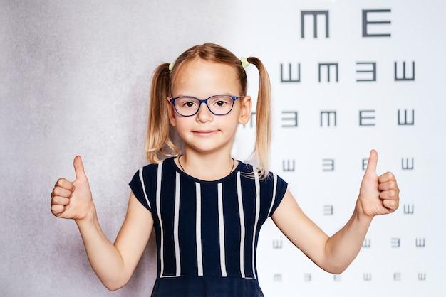 Маленькая девочка в очках с большими пальцами руки принимает тест на зрение перед школой или детским садом с размытой диаграммой зрения на заднем плане