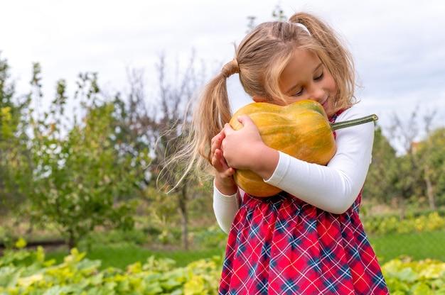 Bambina che indossa un abito di flanella e abbraccia una zucca in un campo di fattoria