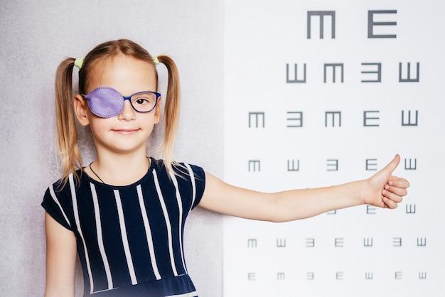 Маленькая девочка в глассе и повязке на глаз или окклюдере с поднятым вверх большим пальцем и размытой глазной диаграммой на заднем плане, лечение амблиопии (ленивого глаза)