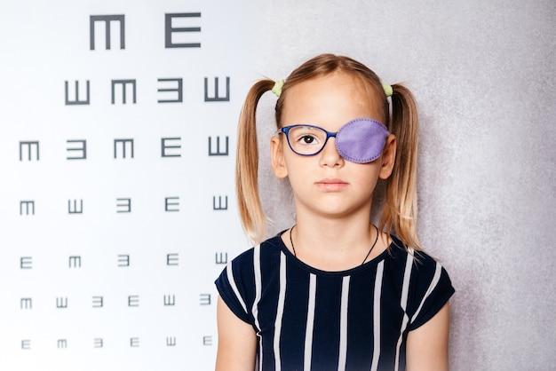 Маленькая девочка в очках и повязке на глаз или окклюдере на фоне размытой диаграммы зрения, лечение амблиопии (ленивого глаза)