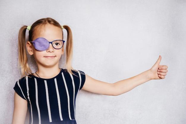 Маленькая девочка в очках и повязке на глаз или окклюдере с поднятым вверх большим пальцем, лечение амблиопии (ленивого глаза)