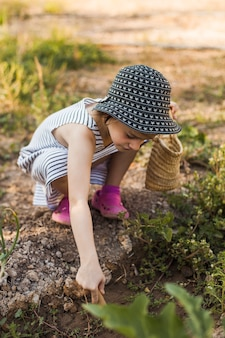 Little girl wearing hat crouching in the vegetable garden