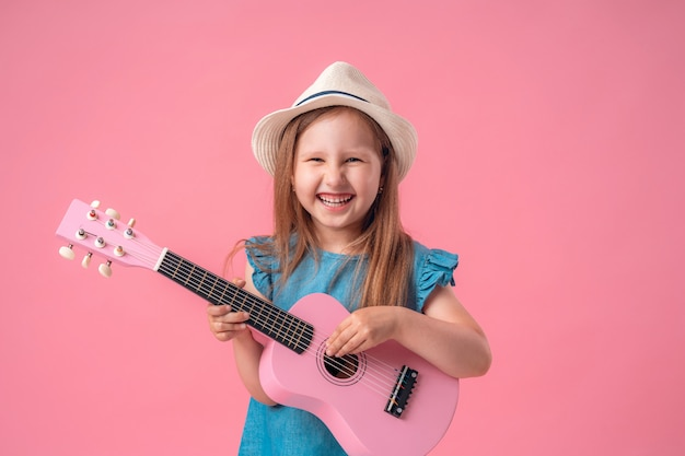 Little girl wearing a hat and a ukulele guitar
