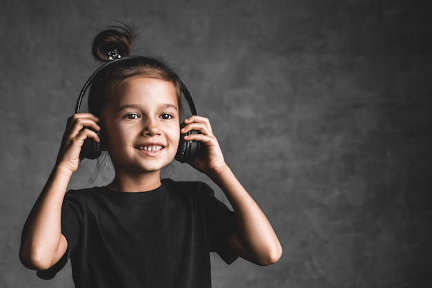 Little girl wearing headphones standing isolated on grey wall listening to music