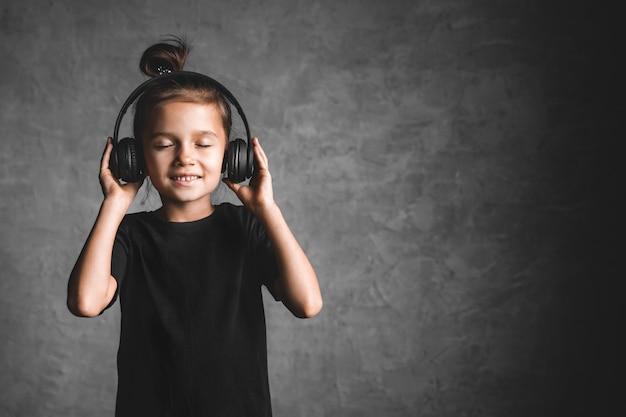 Маленькая девочка в наушниках стоя изолирована на серой стене, слушая музыку