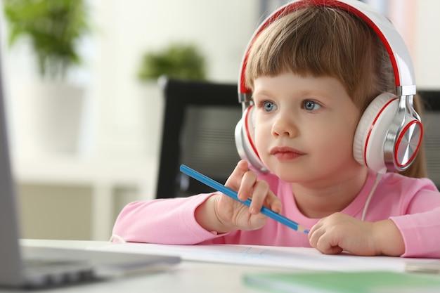 Маленькая девочка в наушниках использует мобильный компьютер