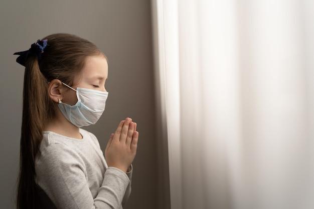 Covid-19を保護するためのマスクを身に着けている少女。彼女は朝、世界のコロナウイルスに対する新しい日の自由を祈っています。神に感謝を祈る少女の手