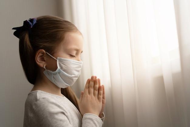 Covid-19を保護するためのマスクを身に着けている少女。彼女は朝、世界のコロナウイルスに対する新しい日の自由を祈っています。神に感謝を祈る少女の手 Premium写真