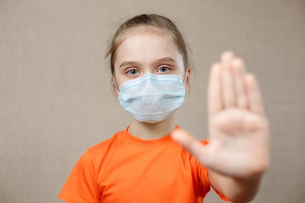 保護のためのマスクを身に着けている女の子。一時停止の標識を表示しています。ウイルスと流行病を阻止しなさい。コロナウイルスcovid-19.stay at home stay safe concept。セレクティブフォーカス。
