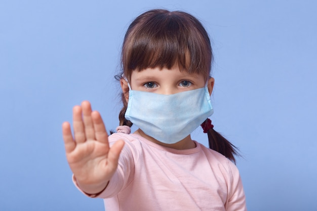 Little girl wearing medical face mask and making stop sign with her palm