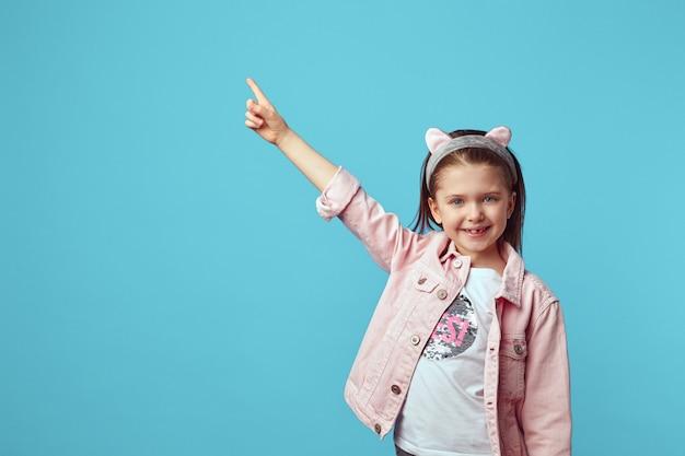 Маленькая девочка в розовой куртке улыбается и указывает на свободное пустое пространство