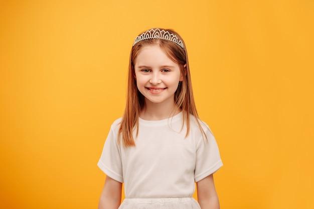 Маленькая девочка в диадеме принцессы смотрит в камеру и улыбается на желтом фоне