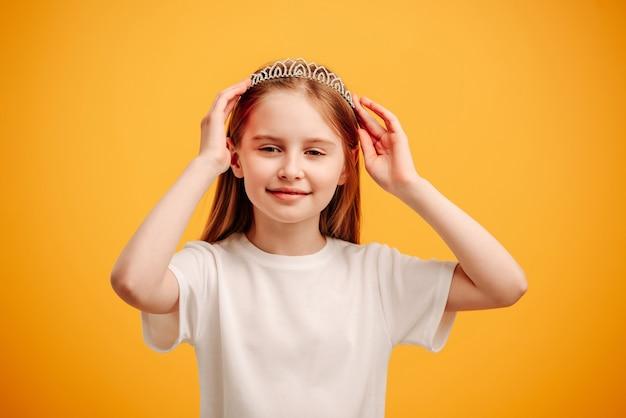 Маленькая девочка в диадеме принцессы смотрит в камеру, изолированную на желтом фоне