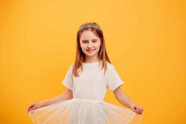 Маленькая девочка в платье принцессы и диадеме смотрит в камеру, изолированную на желтом фоне