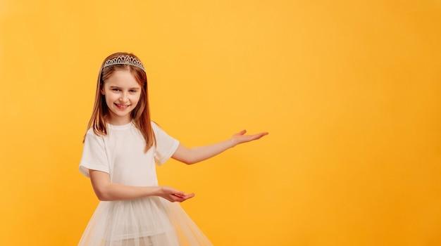 Маленькая девочка в платье принцессы и диадеме позирует изолированной на желтом фоне