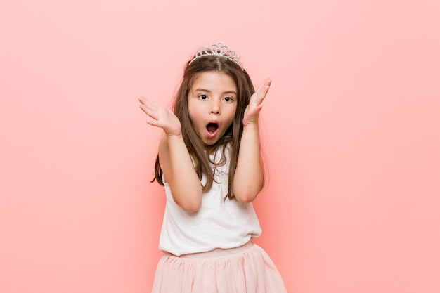 Little girl wearing a princess look celebrating a victory or success, he is surprised and shocked.
