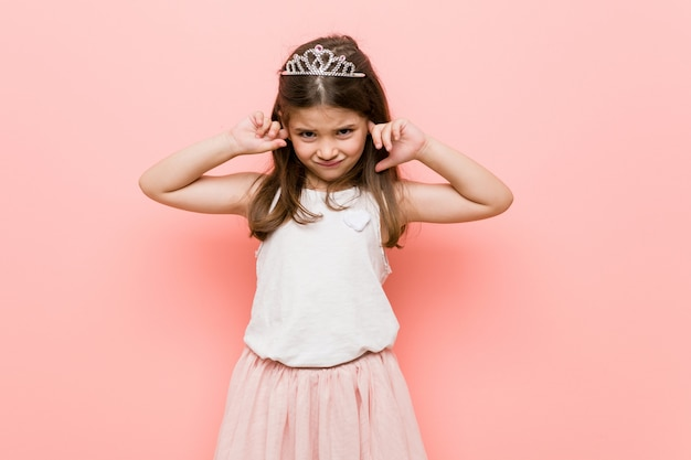 Little girl wearing a princess look covering ears with hands.