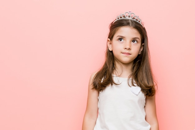 Little girl wearing a princess look dreaming of achieving goals and purposes