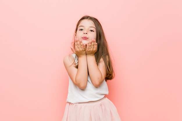 Little girl wearing a princess look folding lips and holding palms to send air kiss
