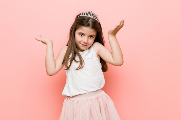 Little girl wearing a princess look makes scale with arms, feels happy and confident