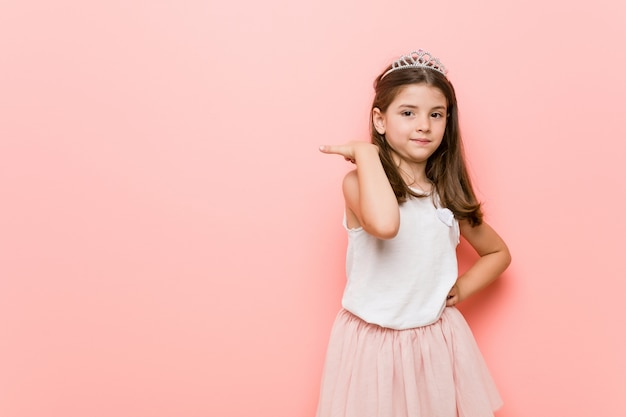 Little girl wearing a princess look points with thumb finger away, laughing and carefree.