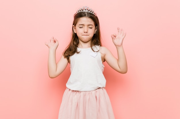 Little girl wearing a princess look relaxes after hard working day, she is performing yoga.