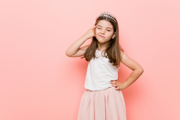 Little girl wearing a princess look showing a disappointment gesture with forefinger.