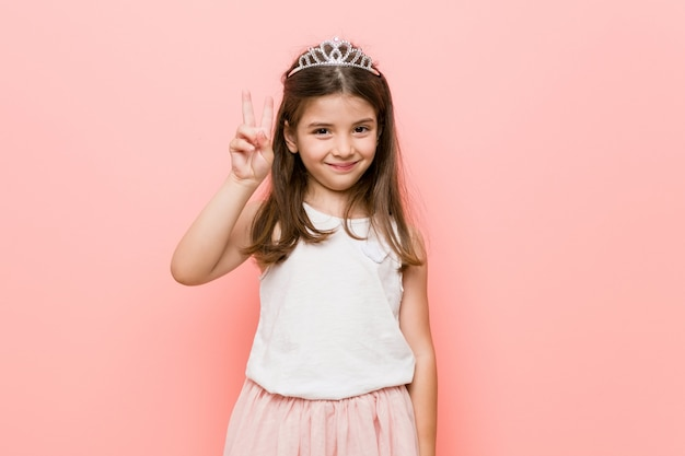 Little girl wearing a princess look showing number two with fingers.