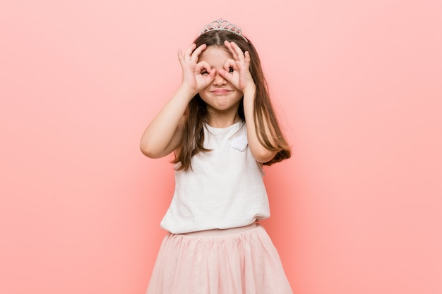 Little girl wearing a princess look showing okay sign over eyes
