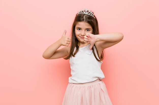 Little girl wearing a princess look showing thumbs up and thumbs down, difficult choose