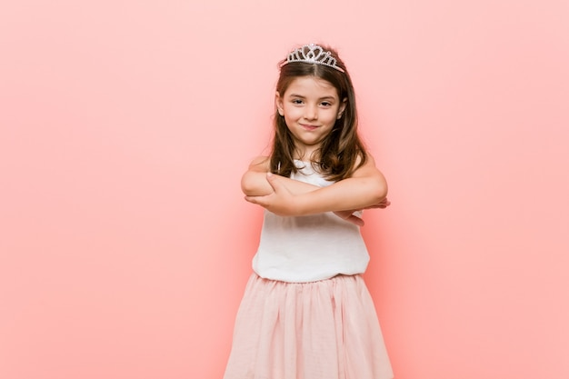 Little girl wearing a princess look smiling confident with crossed arms.