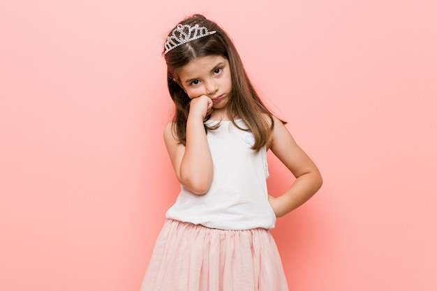 Little girl wearing a princess look who feels sad and pensive, looking at copy space.