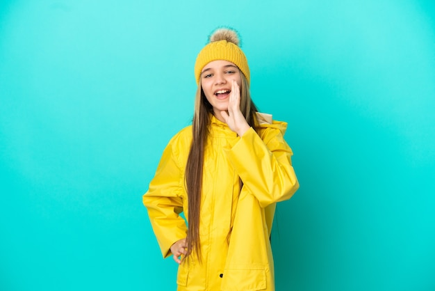 Little girl wearing a rainproof coat over isolated blue background shouting with mouth wide open