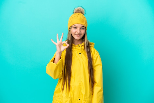 Little girl wearing a rainproof coat over isolated blue background showing ok sign with fingers