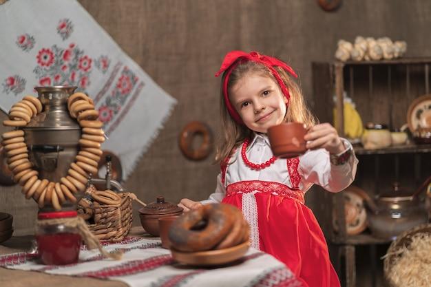 マスレニツァを祝うサモワールからお茶を飲む赤いヘッドバンドと装飾用のシャツを着ている少女