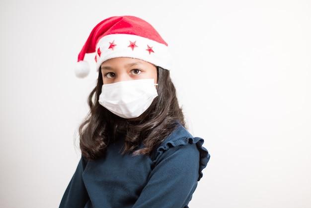 サンタの帽子と白い背景で悲しいカメラを探しているフェイスマスクを身に着けている少女。
