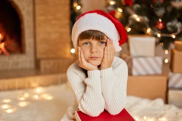 クリスマスツリーの近くに座っているサンタの帽子と白いセーターを着た少女と物思いにふける表情のプレゼントボックスのスタックは、あごの下に手を保ちます。