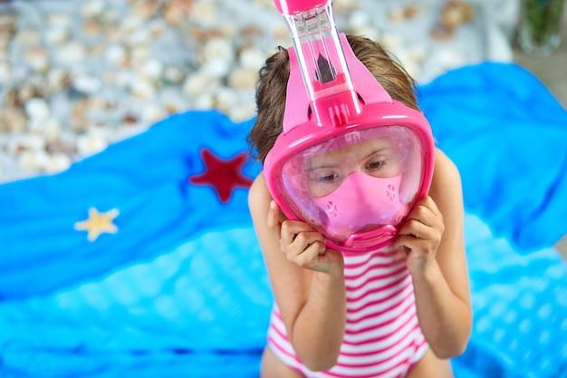 シュノーケリングマスクを身に着けている少女は架空の海やビーチの近くの海で泳ぐことを模倣します
