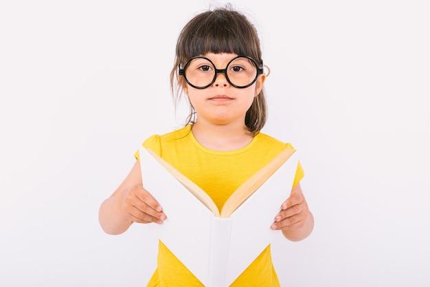 Маленькая девочка в желтой футболке и круглых черных очках держит в руках открытую книгу на белом фоне