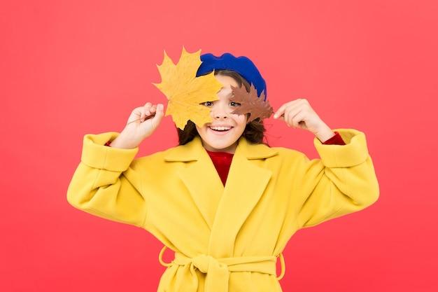Маленькая девочка приветствует осенний сезон. малыш девушка милое лицо держать кленовый лист. наслаждайтесь сезоном. ребенок с осенними желтыми листьями. наступила осень. маленькая девочка носит осенний наряд на красном фоне. привет, сентябрь.