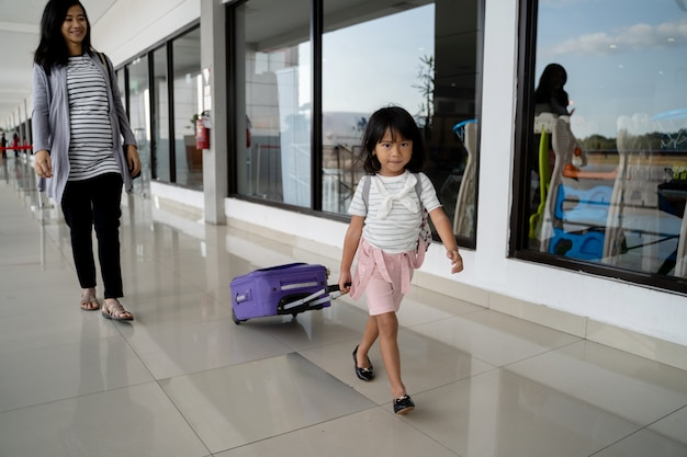 The little girl went with her mother while pulling a suitcase