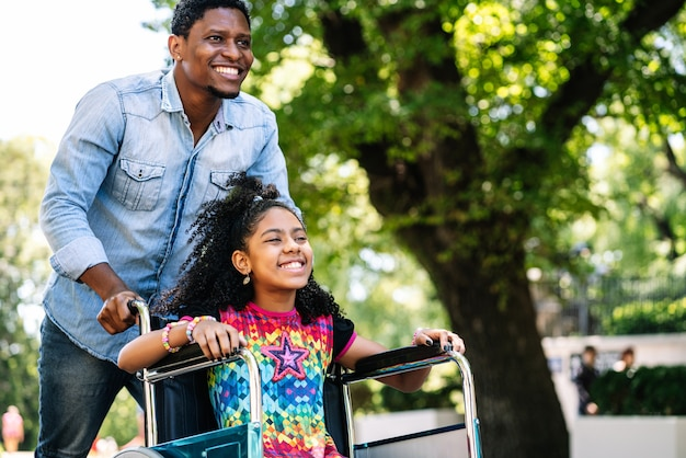 A little girl in a wheelchair enjoying and having fun with her father while on a walk together outdoors
