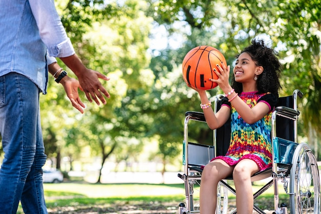 A little girl in a wheelchair having fun with her father while playing basketball together at park