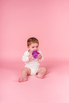 Little girl in a white bodysuit sits with a water bottle